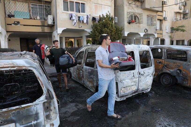 Mieszkańcy Izraela przechodzą między zniszczonymi w ostrzale rakietowym autami /PAP/EPA