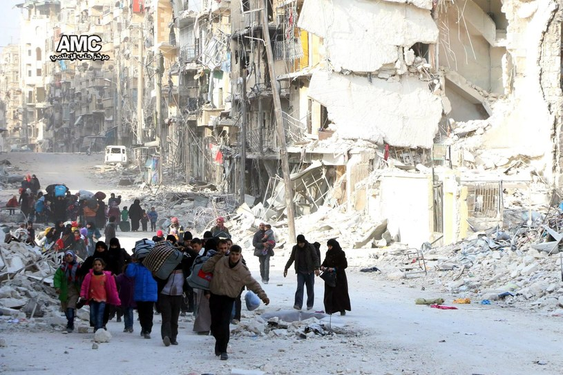Mieszkańcy zdewastowanego przez bomby miasta Aleppo w Syrii /PAP/EPA