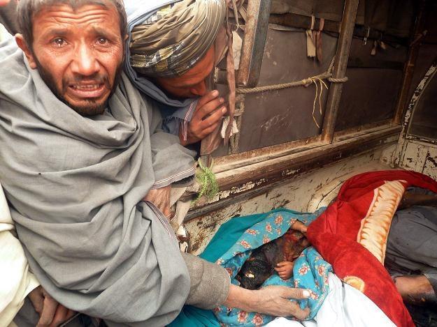 Mieszkaniec wioski pokazuje ciała zabitych /PAP/EPA