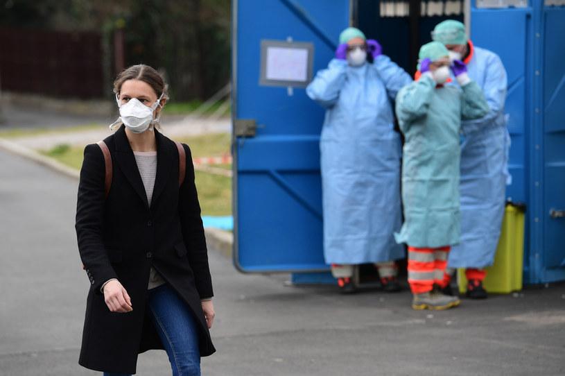 Mieszkanka Brescii, a w tle pracownicy medyczni /AFP