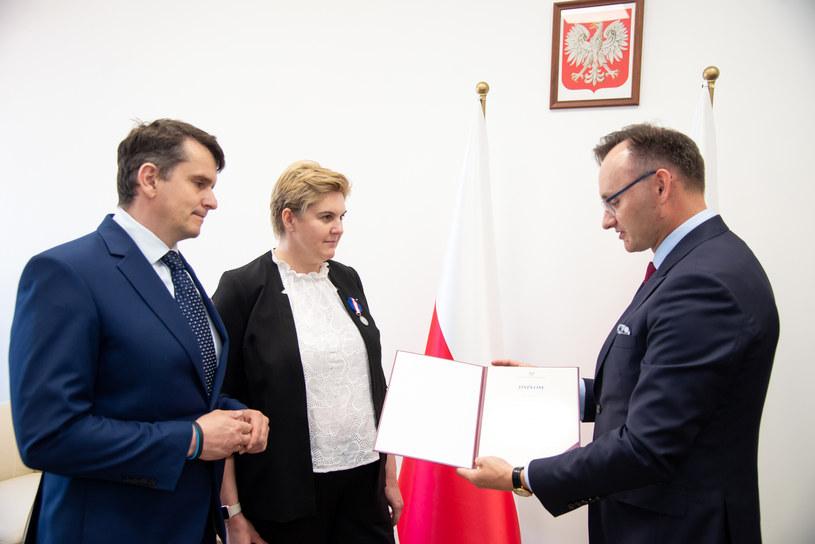 Mikołaj Pawlak wręcza honorową odznakę Katarzynie i Mateuszowi Kłoskom /Rzecznik Praw Dziecka /Archiwum