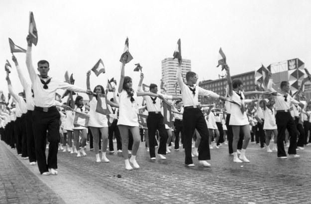 Młodzież wykonująca układy gimnastyczne z chorągiewkami podczas przemarszu ulicą Marszałkowską w Warszawie /Z archiwum Narodowego Archiwum Cyfrowego