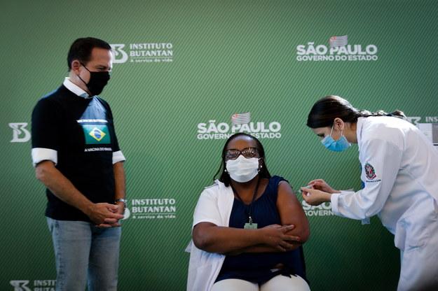 Monica Calazans (C), pielęgniarka w Hospital las Clinicas w stolicy Sao Paulo, otrzymuje szczepionkę przeciwko COVID-19 w obecności gubernatora stanu Sao Paulo, Joao Doria (L), w Sao Paulo w Brazylii /FERNANDO BIZERRA JR. /PAP/EPA