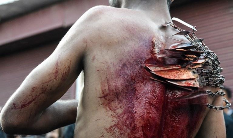 Muzułmanin samobiczujący się podczas święta Aszura /AFP
