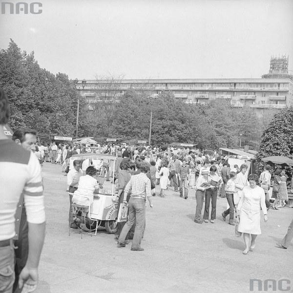 Uczestnicy kiermaszu książek w Warszawie. Na pierwszym planie widoczna kobieta sprzedająca wodę z saturatora wózkowego.