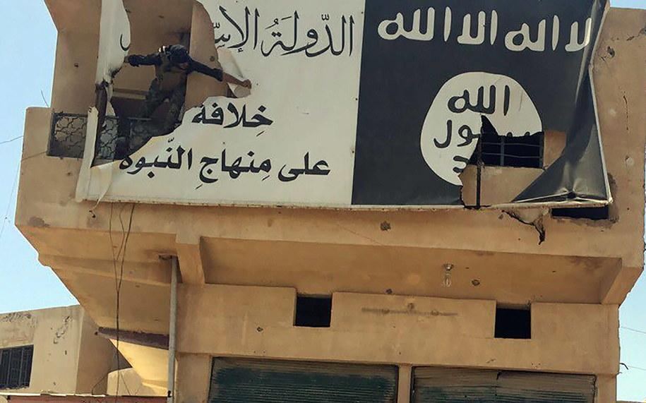 Na zdjęciu archiwalnym z 07.06.2016 roku iracki żołnierz zrywa z budynku flagę tzw. Państwa Islamskiego (zdjęcie ilustracyjne) /Abbas Mohammed /PAP/EPA