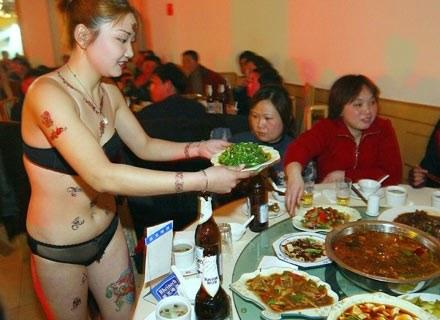 Na zdjęciu: kelnerka ubrana tylko w bieliznę obsługuje klientów restauracji w Nanjing, styczeń 2003 /AFP