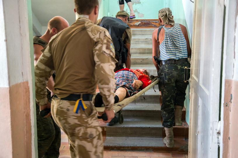 Na zdjęciu koledzy niosą rannego żołnierza w Szczastii, 20 sierpnia 2014 /OLEKSANDR RATUSHNIAK /AFP