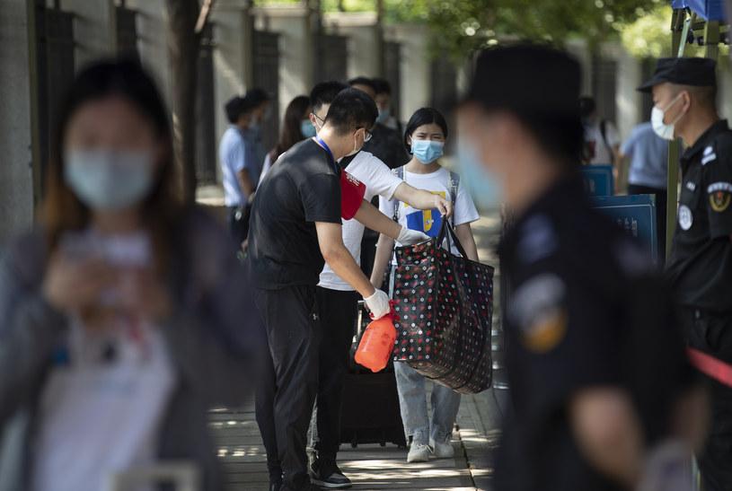 Na zdjęciu: Kontrola studentów powracających do kampusu uniwersytetu w Wuhan / STR   /AFP