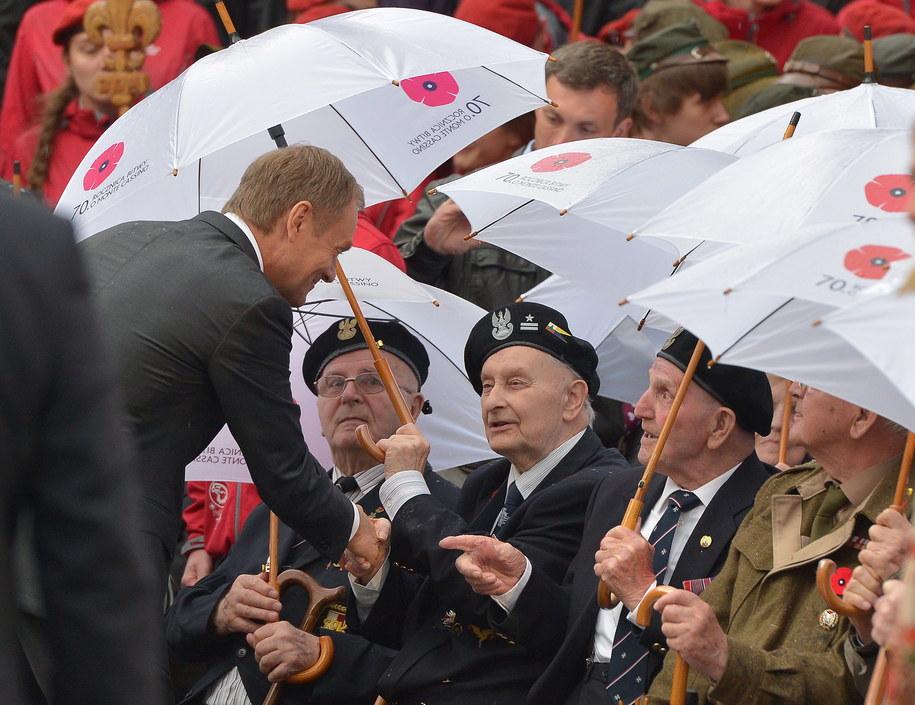 Na zdjęciu premier Donald Tusk (z lewej) wita się z kombatantami w trakcie uroczystości na dziedzińcu opactwa Benedyktynów /Radek Pietruszka /PAP