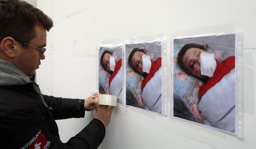 Na zdjęciu protestujący rozkleja plakaty ze zdjęciem pobitej dziennikarki /SERGEY DOLZHENKO /EPA