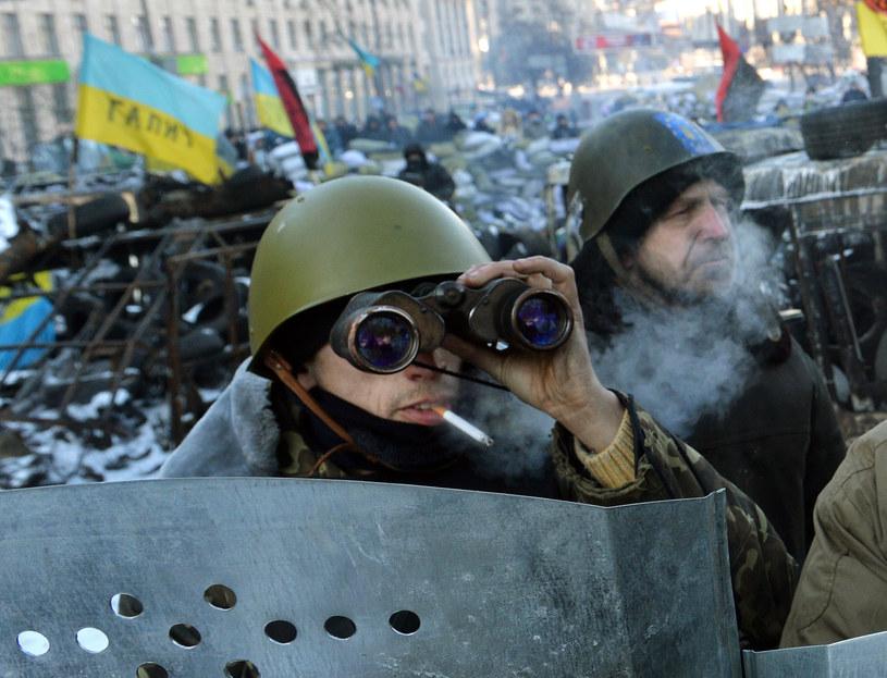 Na zdjęciu protestujacy za barykadą na jednej z ulic Kijowa /SERGEI SUPINSKY /AFP