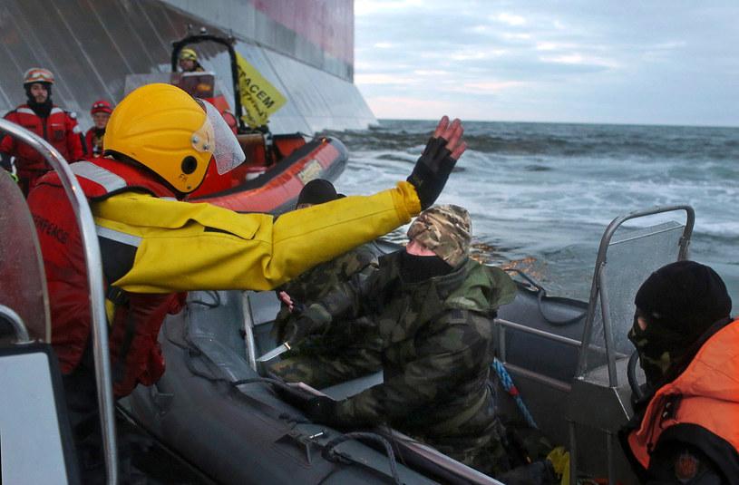 Na zdjęciu zamaskowani funkcjonariusze Rosyjskiej Straży Przybrzeżnej dokonują abordażu na statek Greenpeace /DENIS SINYAKOV /AFP