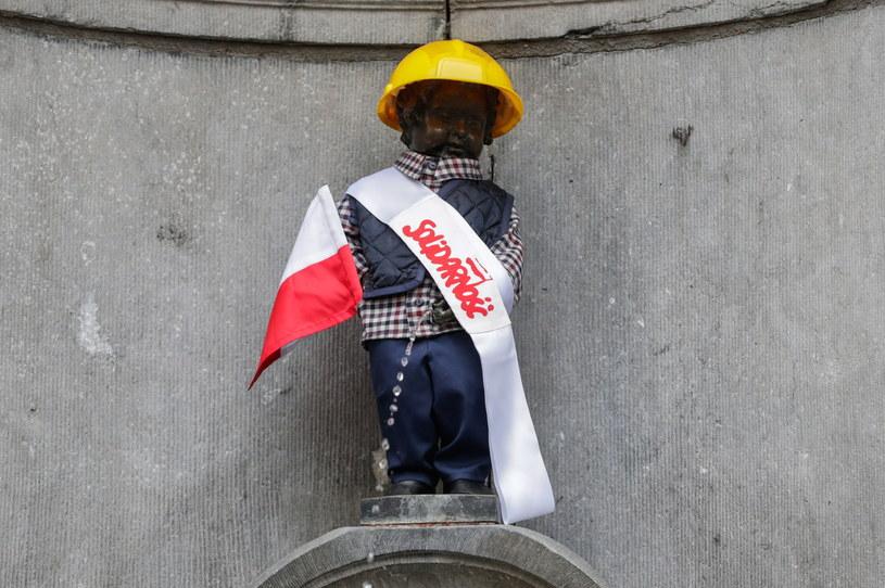 """Najsłynniejszy pomnik w Belgii, figurka Manneken Pis przedstawiająca siusiającego chłopca została w poniedziałek ubrana w strój stoczniowca i szarfę z napisem """"Solidarność"""". /STEPHANIE LECOCQ  /PAP/EPA"""