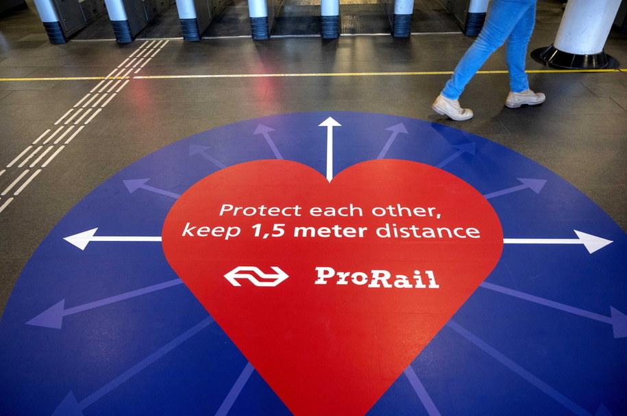 Naklejka na peronie dworca w Amsterdamie zachęcająca do utrzymywania dystansu /EVERT ELZINGA    /PAP/EPA