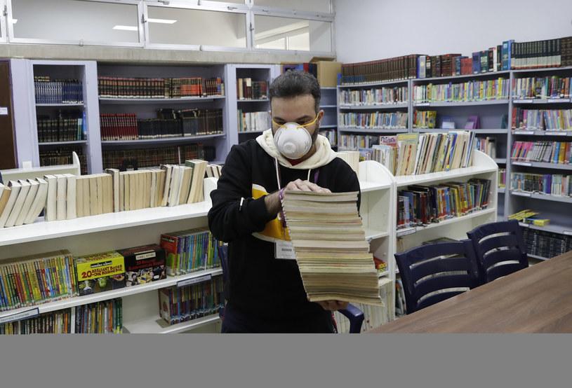 Nauczyciel trzyma stertę książek ze szkolnej biblioteki, która jest dezynfekowana w związku z epidemią koronawirusa. /Hussein Malla /East News
