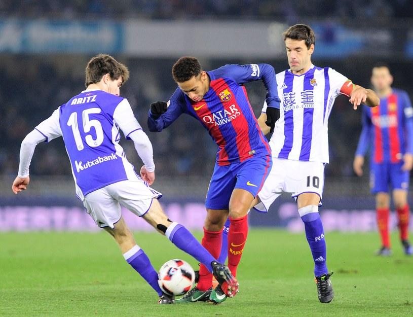 Neymar (w środku) oraz piłkarze Realu Sociedad - Aritz Elustondo (z lewej) i Xabier Prieto /AFP