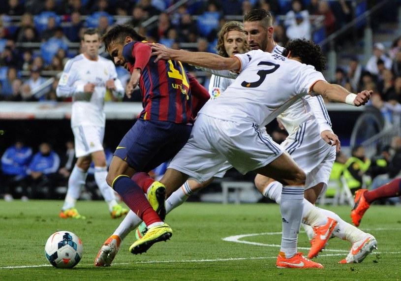 Neymar z Barcelony w walce z piłkarzami Realu Madryt /AFP