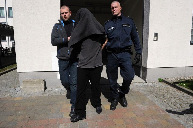Niemieccy policjanci wyprowadzają z aresztu zatrzymanego Adriana M. /Marcin Bielecki /PAP