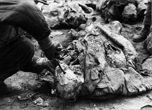 Niemiecki ekspert ogląda ciało zamordowanego w katyńskim lesie Polaka, kwiecień 1943 r. /East News