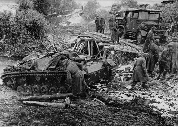 Niemieckie działo samobieżne StuG III przejeżdża przez błotnisty teren na froncie wschodnim. Widoczna także ciężarówka jadąca po drewnianym moście /Z archiwum Narodowego Archiwum Cyfrowego