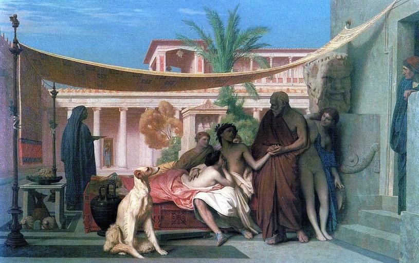 """Niewiele wiadomo o życiu Aspazji. Na pewno związana była z Peryklesem, ateńskim wodzem, który porzucił dla niej własną żonę. Przez jej wpływ na polityka, obywatele Aten oskarżali ją o uprawianie nierządu. Na ilustracji obraz Jean-Léona Gérôme'a """"Sokrates szukający Alcybiadesa w domu Aspazji"""" (domena publiczna))"""