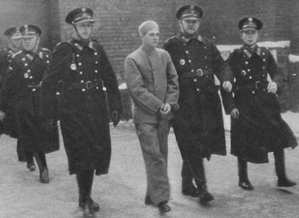 """Nikifor Maruszeczko eskortowany przez policjantów fot. """"Światowid"""" /Wikimedia"""