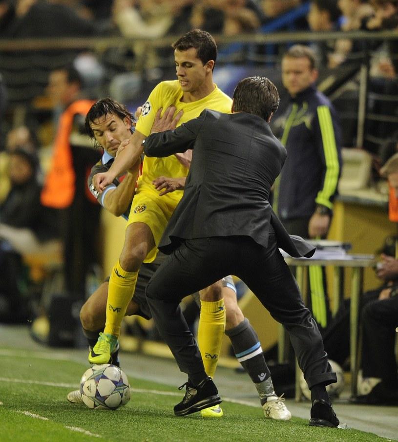Nilmar (na żółto) przepycha się z trenerem Napoli Walterem Mazzarrim. /AFP