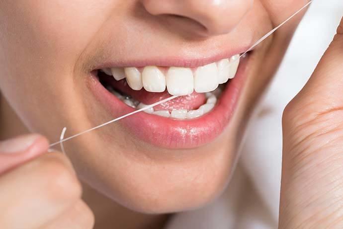 nitkowanie zębów /© Photogenica