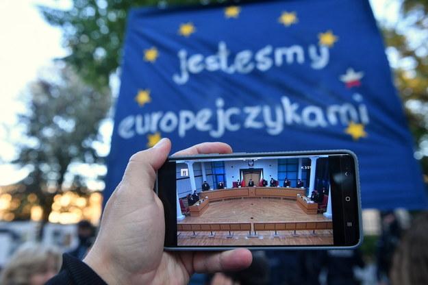 Obrady TK oglądane na ekranie telefonu przed siedzibą Trybunału Konstytucyjnego w Warszawie /Radek Pietruszka /PAP