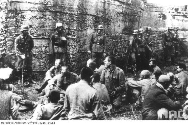 Jeńcy polscy przed jednym z bunkrów na Westerplatte pilnowani przez niemieckich żołnierzy