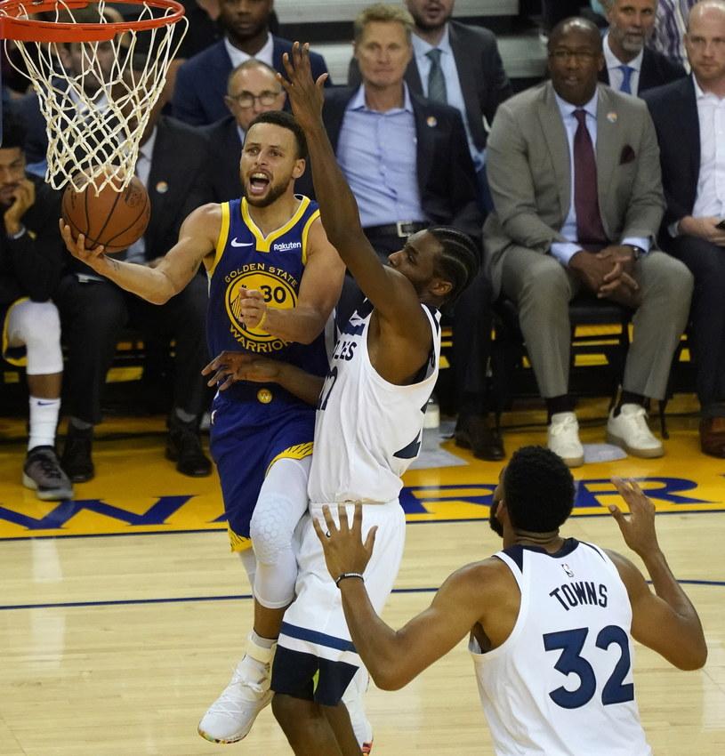 Obrońca Golden State Warriors Stephen Curry (L) w meczu z Minnesota Timberwolves. Andrew Wiggins (w środku) i center Karl-Anthony Towns (P). /PAP/EPA