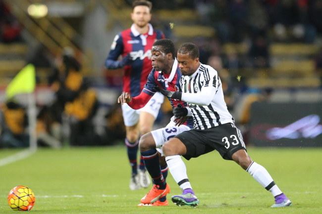 Obrońca Juventusu Patrice Evra (z prawej) w walce z pomocnikiem Bologny Godfredem Donsahem /PAP/EPA