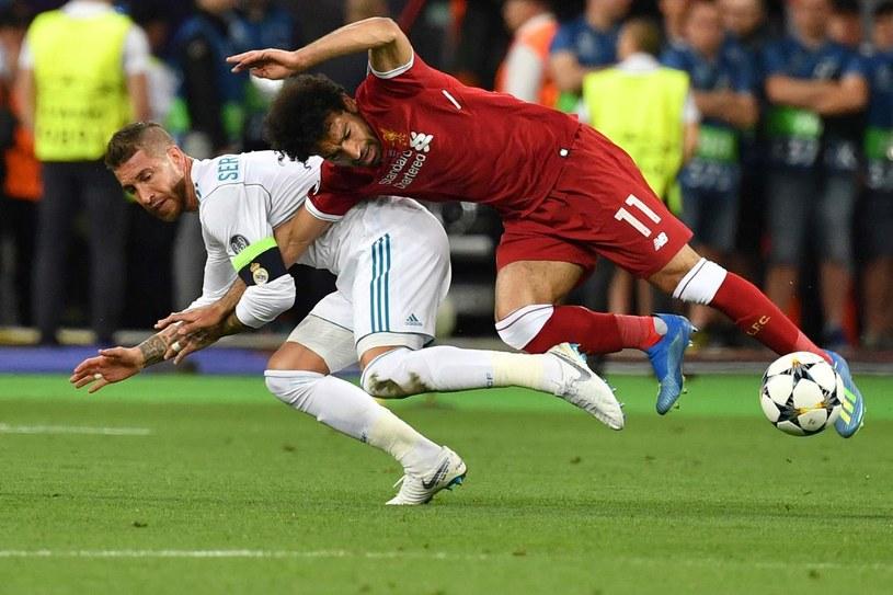 Obrońca Realu Madryt Sergio Ramos przytrzymuje Mohameda Salaha. Gwiazda Liverpoolu przypłaciła to starcie kontuzją /AFP