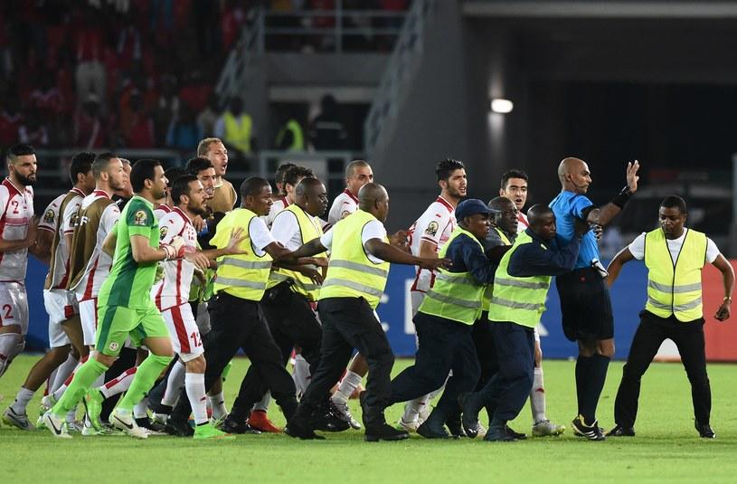 Ochroniarze bronią sędziego przed piłkarzami Tunezji /AFP