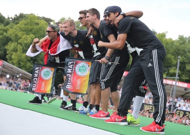 Od lewej: Lukas Podolski, Per Mertesacker, Mesut Oezil, Ron-Robert Zieler, Jerome Boateng i Sami Khedira świętują z kibicami pod Bramą Brandenburską /PAP/EPA