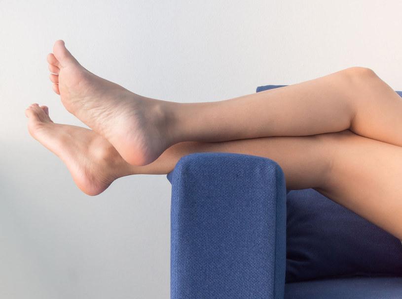 Odpoczynek z nogami w górze poprzedzony naprzemiennym prysznicem złagodzi rozpierający ból /123RF/PICSEL