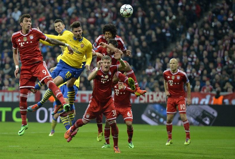 Olivier Giroud (żółta koszulka) strzela głową na bramkę Bayernu /AFP