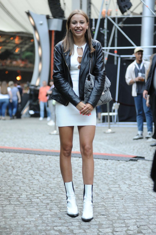 Oliwia Bieniuk do obcisłej białej sukienki z odważnym dekoltem dobrała czarną skórzaną kurtkę i białe kozaczki /East News
