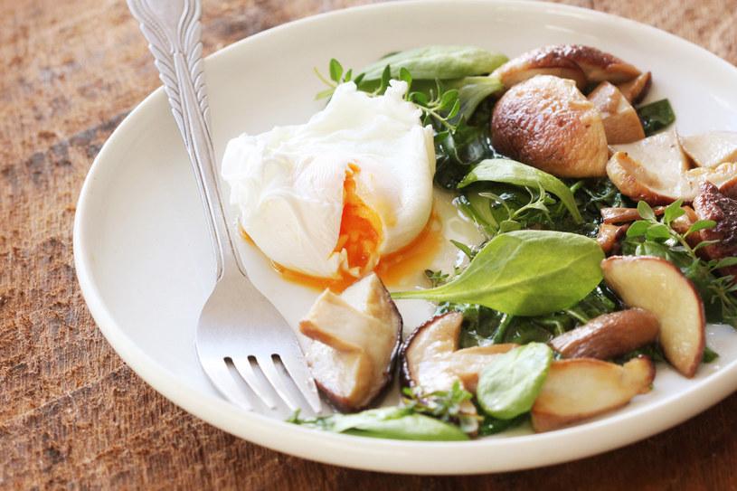 Oryginalny pomysł na szybkie śniadanie: cieniutko pokrojone grzyby  z jajkiem w koszulce posypane świeżymi ziołami albo jadalnymi kwiatami /123RF/PICSEL