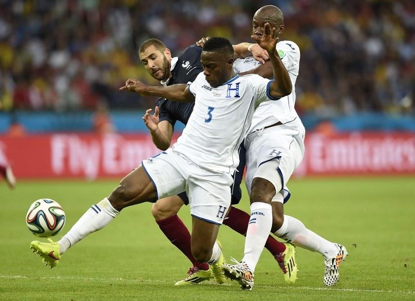 Osman Chavez (z prawej) blokuje na MŚ w Brazylii Karima Benzeme, by Maynor Figueroa mógł spokojnie opanować piłkę. /AFP
