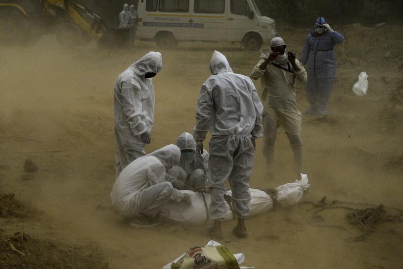 Osoby w kombinezonach ochronnych nad ciałem zmarłego na COVID-19, Indie, New Dehli, maj 2020 /SAJJAD HUSSAIN / AFP /AFP