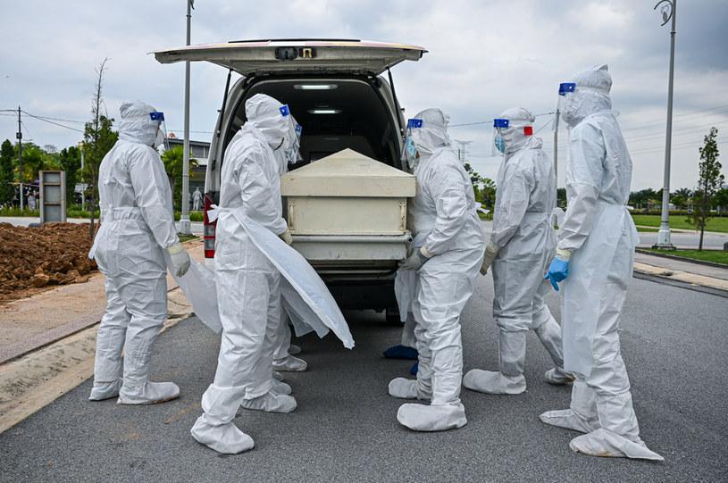 Osoby w strojach ochronnych przenoszą trumnę zmarłego na COVID-19 /MOHD RASFAN / AFP /AFP