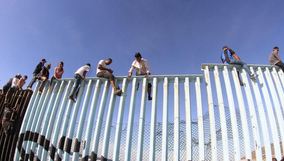 Osoby z karawanu przechodzą przez ogrodzenie w Tijuanie /Joebeth Terriquez /PAP/EPA