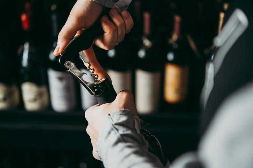 Otwieranie wina korkociągiem /©123RF/PICSEL