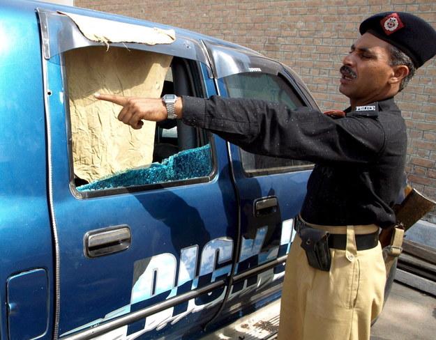 Pakistański policjant pokazuje samochód, którym jechał polski inżynier Piotr Stańczak, gdy został zaatakowany przez talibów /SHABBIR HUSSEIN /PAP/EPA