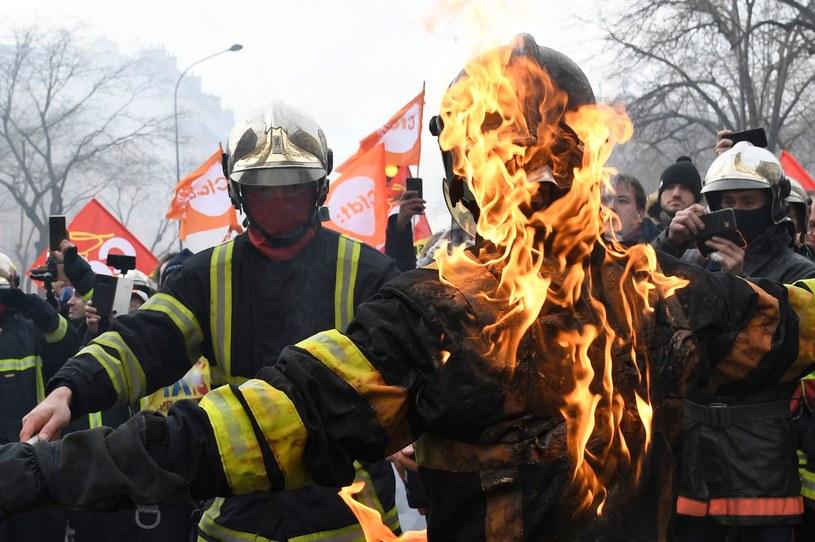 Palący się strażacy podczas manifestacji w Paryżu /AFP