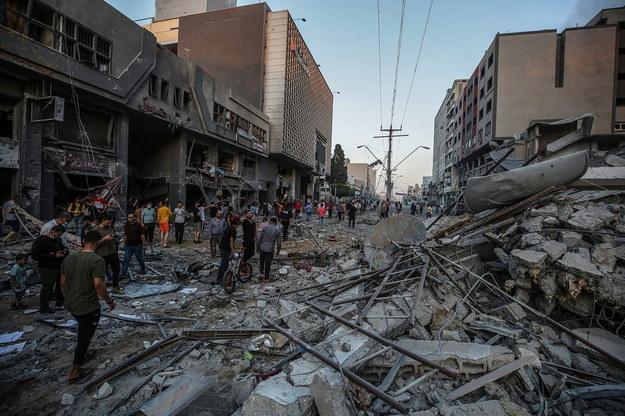 Palestyńczycy sprawdzają gruzy zniszczonej wieży Al-Shorouq po izraelskim uderzeniu w Strefie Gazy /MOHAMMED SABER  /PAP/EPA