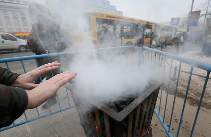 Pasażer ogrzewa ręce przy koksowniku na przystanku autobusowym /Paweł Supernak /PAP