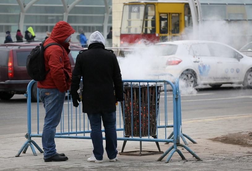 Pasażerowie ogrzewają się przy koksowniku na przystanku autobusowym na Placu Bankowym w Warszawie /Paweł Supernak /PAP